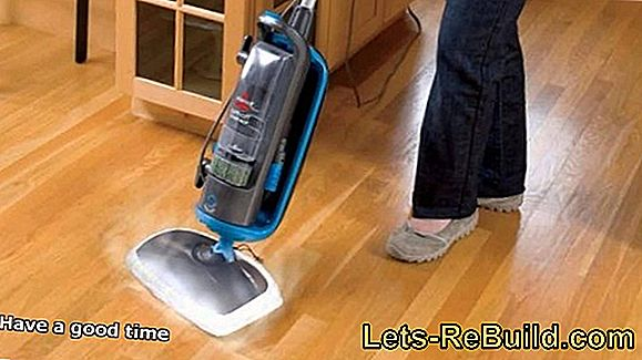 Steam cleaner on the wooden floor